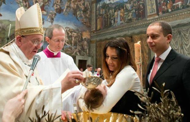El Papa Francisco, bautizando a un niño.,