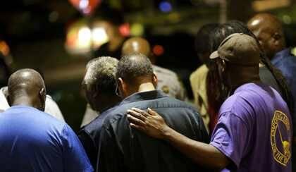 Miembros de la iglesia oran en un parking frente al templo atacado  / Associated Press, David Goldman
