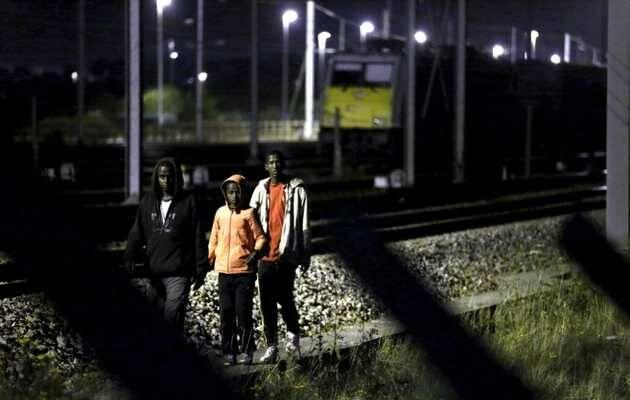 Tres jóvenes inmigrantes junto a las vías de tren para intentar acceder al túnel del Canal / Reuters,inmigrantes, Canal de la Mancha