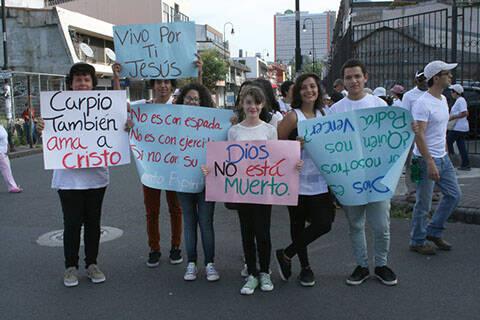Jóvenes participando con carteles diversos. / Maranata