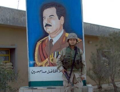 Una militar de la coalición occidental frente a un cartel de Saddam Hussein. Foto: ventolinmono (Flickr,CC)
