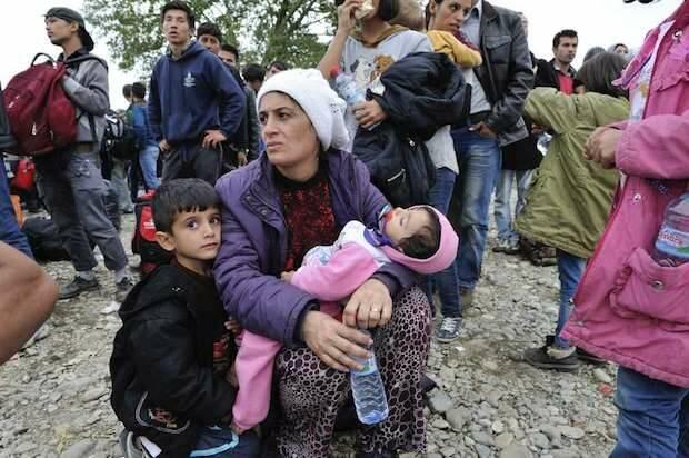 Una madre y sus hijos esperan junto a otros refugiados para entrar en el centro de recepción de Vinojug en Gevgelija. © ACNUR/M.Henley.,