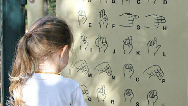 Niña frente a abecedario en lengua de signos. / Flickr, SaraSmo,
