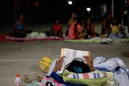 Dormir a la intemperie no impide que esta persona siga leyendo su Biblia.