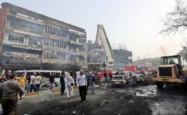 Ciudadanos iraquíes se congregan alrededor del edificio que ha quedado destrozado por la explosión de un coche bomba en Bagdad. / EFE,