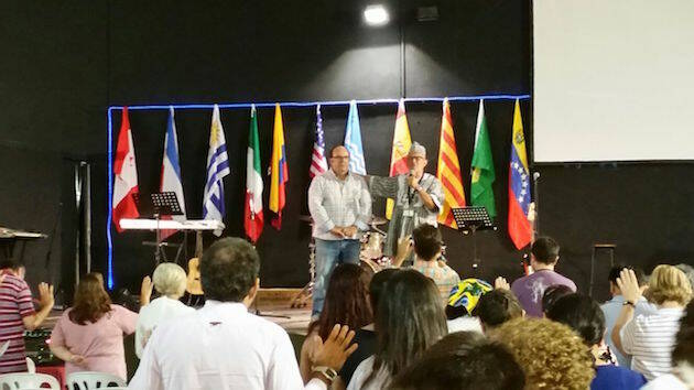 El pastor Juan Antonio López, con atuendos típicos de Burjina Faso, ora por el ex parlamentario Rafael Luna. / FADE,fade cataluña
