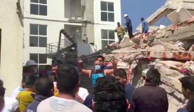 Un rescatista pide silencio durante las labores de búsqueda de supervivientes en un edificio desplomado por el terremoto. / Univision,