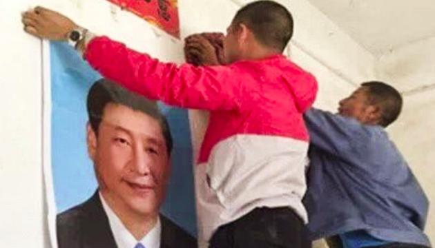 Unos jóvenes colocan el retrato de Xi Jinping, en Yugan. / Lvv2.com, South China Morning Post,