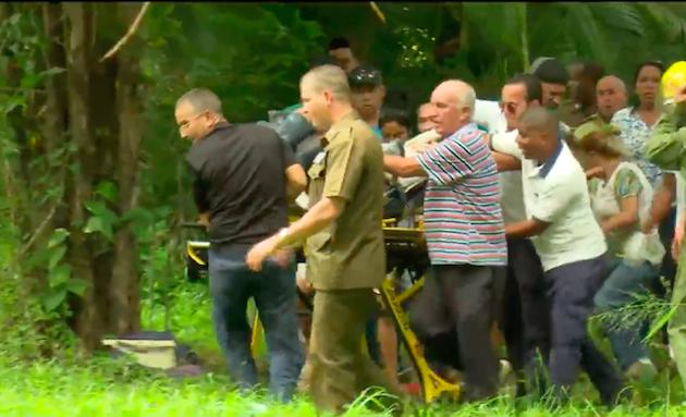 Miembros de equipos de rescate junto a vecinos de la zona, ayudando a transportar a uno de los heridos. / Captura Youtube CubaTV,