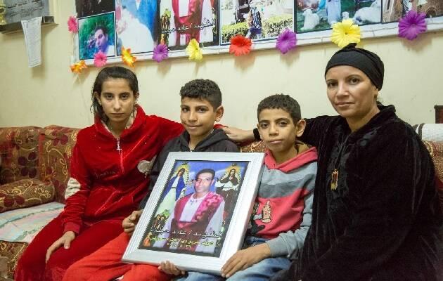 Marco y Mina, en el centro, junto a su madre y su hermana, con una foto de su padre fallecido  / Puertas Abiertas,