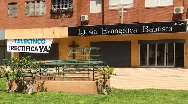 La pancarta ha sido colocada junto al cartel de la iglesia. ,