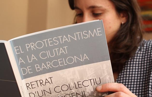 La investigadora Anna Clot ojea uno de los ejemplares del trabajo en un café de Gràcia. / Jonatán Soriano,