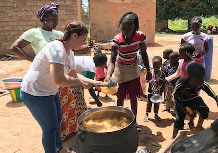 Uno de los grandes problemas en Burkina Faso es la desnutrición. En la imagen, un cooperante ayuda con la comida que la asociación prepara tres veces por semana./ Fb Cooperando con Burkina Faso