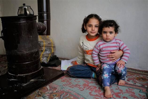 De siete años, Vahide sostiene a su hermana en su casa en Estambul. / © UNHCR, Emrah Gurel,