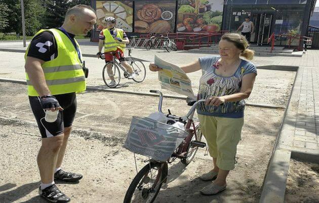 Un ciclista repartiendo el periódico Kolokol-The Bell a una mujer. / Kolokol-The Bell,