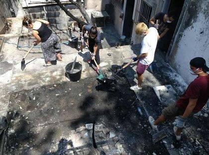 Equipos de cristianos están ayudando con la limpieza de las propiedades quemadas. / Nikos Stamoulis.