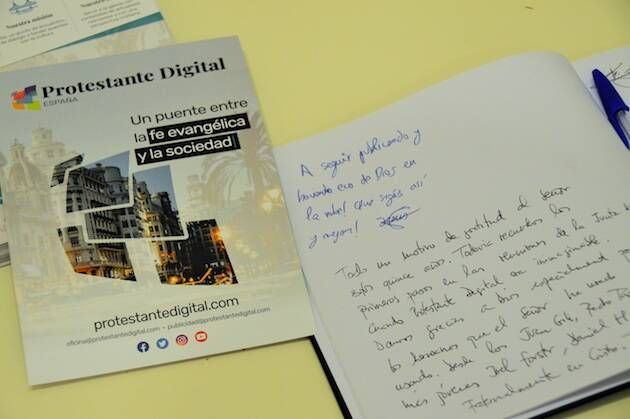 Un folleto de Protestante Digital y el libro donde los asistentes felicitaron al medio por sus 15 años. / Jordi Torrents,