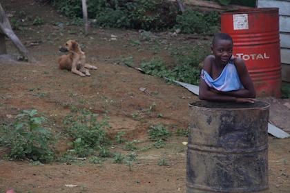 Una niña observa a los visitantes que pasan por delante de su casa, en la aldea de Movun. / Jonatán Soriano