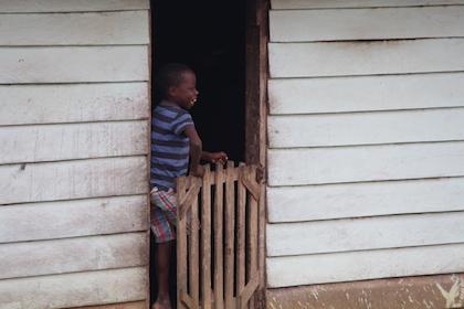 Un niño ríe desde la puerta de su casa, en Movun, después de que un vecino le haya dicho una broma. / Jonatán Soriano