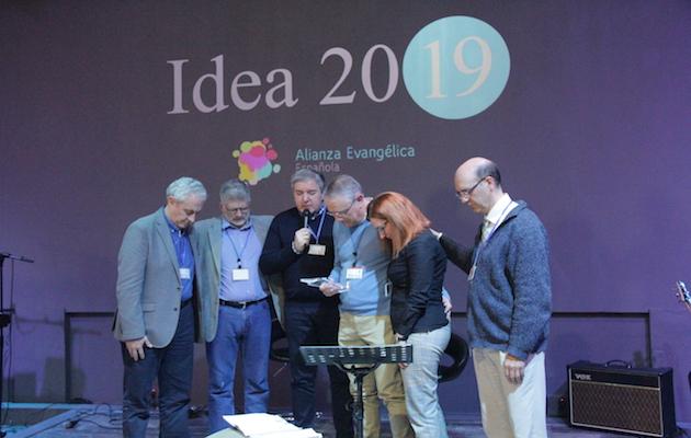 Miembros de la junta de la Alianza orando junto a Jaume Llenas y Puri, su mujer, en el acto de despedida del hasta ahora secretario general. / D. Hofkamp,