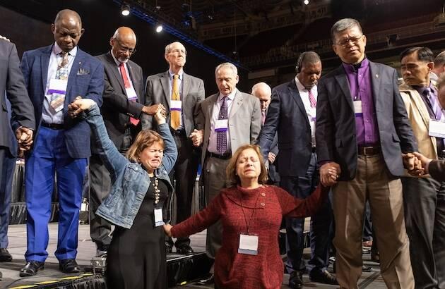Los delegados de la Iglesia Metodista Unida se unen en oración antes de la votación clave. / Mike DuBose, UMNS,