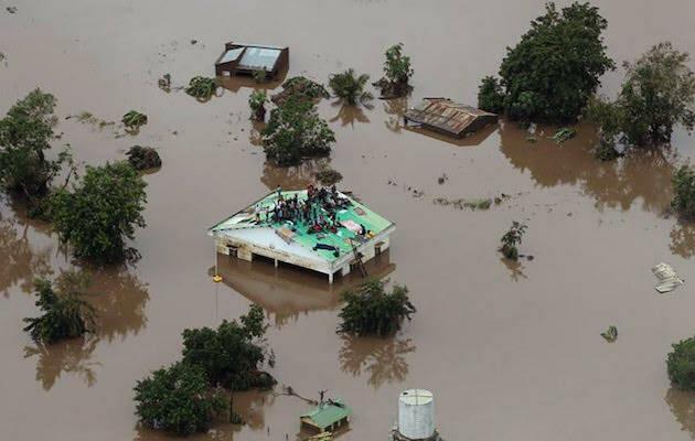 Un grupo de personas subidas al tejado de una casa después de que el agua haya inundado toda la zona. / UEBE,
