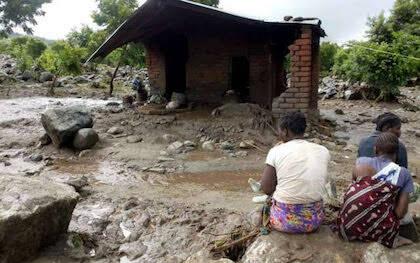 Un grupo de mujeres frente a una casa totalmente destruida. / UEBE