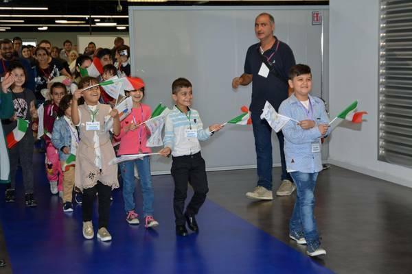 Algunos de los niños, al llegar a Italia, con banderas del país que les acoge. / MediterraneanHope,