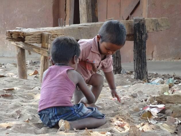 Niños de India escarbando entre basura.,