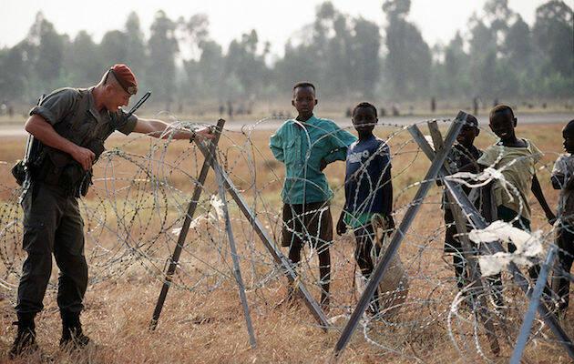 Un soldado de la misión internacional ajustando una alambrada frente a un grupo de niños tutsi refugiados en 1994. / Wikimedia Commons,