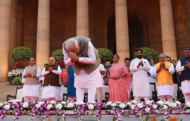 Modi, en primer plano, saludando con algunos de sus ministros al fondo, durante la ceremonia de toma de posesión. / Twitter @narendramodi,