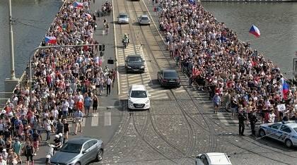 Un flujo constante de personas cruza un puente en Praga para acceder al sitio de la manifestación.