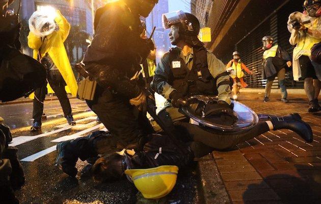Dos policías inmovilizan a una manifestante este domingo en Hong Kong. / Twitter @HongKongFP,