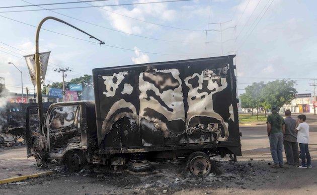 Una camioneta calcinada en las calles de Culiacán. / Twitter @lajornadaonline,