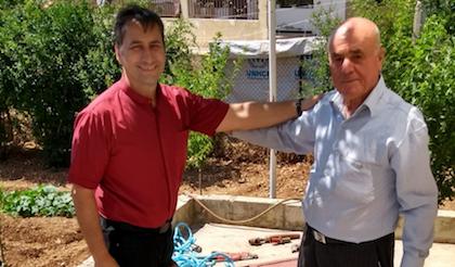 Azzati y Habib celebran la instalacion de una bomba de agua.