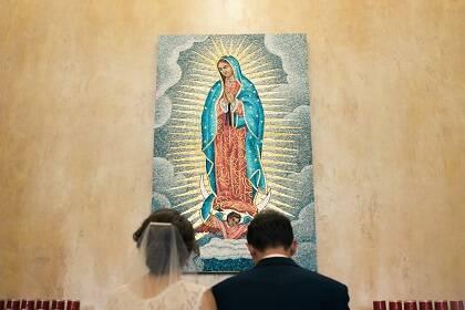 Una pareja reza a una imagen de María en una iglesia. / Josh Applegate, Unsplash CC